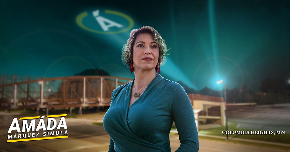 Like a hero, Amáda Márquez Simula looks over the city near the Central Avenue footbridge. A searchlight featuring her circular Á insignia illuminates the night sky.