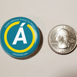 Vote Amáda pin compared to a US quarter